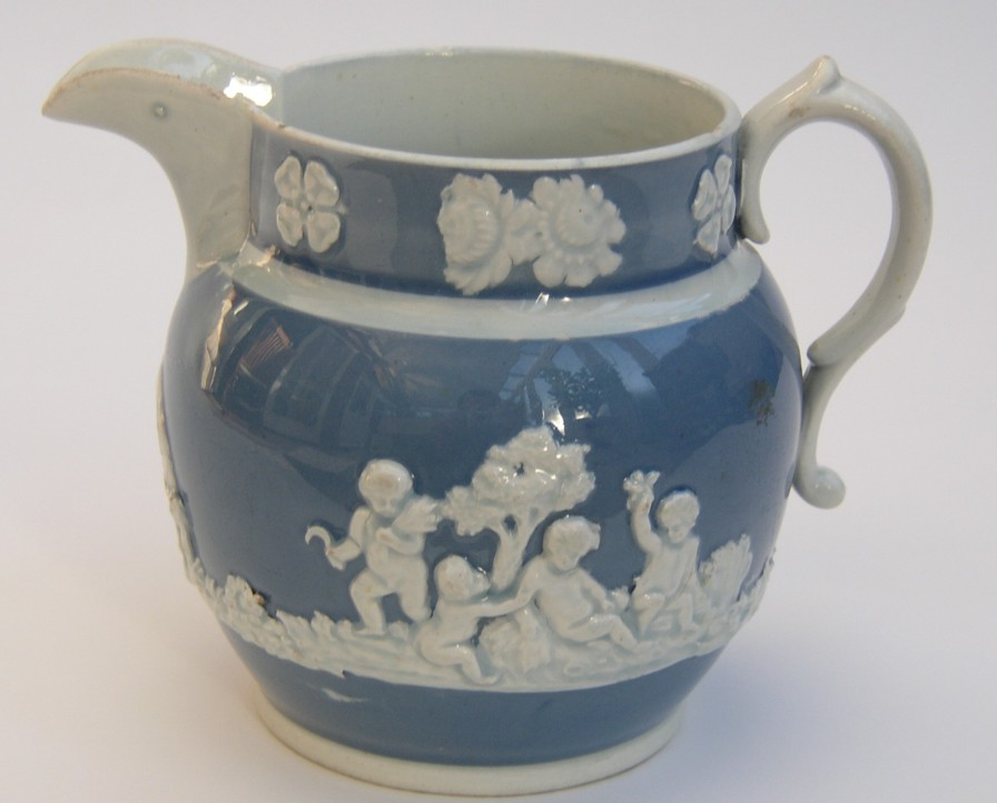 Wood and Caldwell Staffordshire Jug.  Cream colour on the inside, blue on the outside.  Cherubs and horses in the pattern.